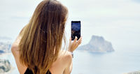 Rear view woman admire view through smartphone screen device, take picture enjoy beauty in nature photographing Penyal d'Ifac Natural Park of Calpe, distance view. Travel destinations, tourism concept