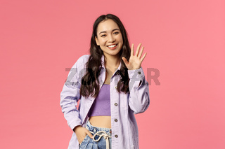 Hello nice to meet you. Cute stylish young girl meet new people at work, waving hand and smiling with little laugh as greeting, saying hi, welcoming newbies, standing pink background