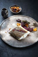Gourmet fried European skrei cod fish filet with algae and vegetable crisps as closeup on a modern design plate