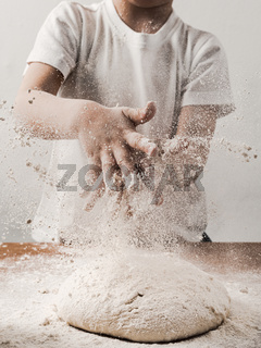 kid clapping hands with flour over dough, vertical