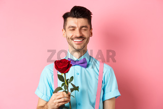 Valentines day and romance concept. Romantic man with red rose going on date with lover, standing in fancy bow-tie on pink background