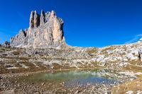 Drei Zinnen spiegeln sich in kleiner Pfuetze, Dolomiten, Suedtirol