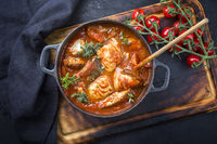 Traditional Brazilian fish stew moqueca baiana with fish filet in tomato sauce as top view in a modern design cast-iron roasting dish