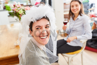 Lachende Braut mit Schleier bei Hochzeit oder Junggesellinnenabschied
