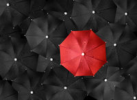 Concept image with lots of black umbrellas and a red umbrella that stands out