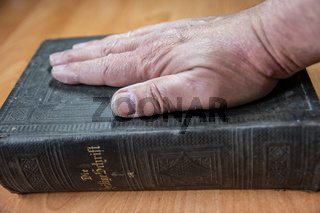 Man puts hand to oath on the Bible