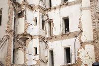 Old demolished multistory building with bricks and doorframes. Demolition, renovation, earthquake concept