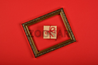 Brown paper giftbox in golden frame on red