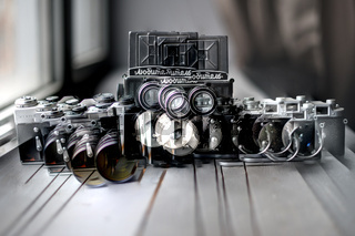 Double exposure Photography, three retro old film photo cameras on wood background, hipster Lifestyle