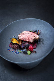 Barbecue dry aged wagyu roast beef natural sliced offered with vegetable chips and forest fruits as closeup on a modern design plate