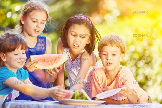 Kinder essen gemeinsam Melone im Sommer