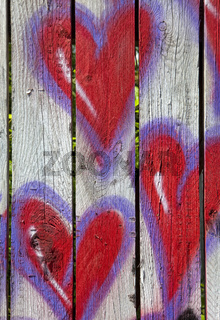 Red hearts painted on a fence
