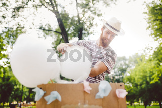 photo theme small business cooking sweets. A young man with a beard of a Caucasian trader in the hat the owner of the outlet makes candy floss, fairy floss or Cotton candy in the summer park