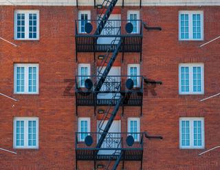 Ziegelfassade mit schwarzer Fluchttreppe aus Stahl