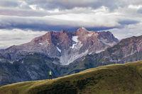 Man hiking on mountain and purple light illuminates landscape and the moody sky. Karkopf, Lechtal Alps, Austria.
