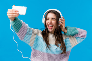 Upbeat, charismatic and happy smiling young gorgeous woman in winter sweater, enjoying awesome music, taking selfie as listening favorite song in headphones, holding smartphone, blue background