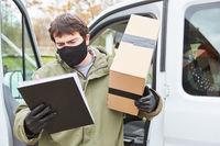 Paketbote mit Paket schaut auf Lieferschein bei Lieferung