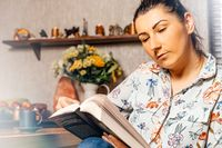 Woman reading a book from comfort of her home during coronavirus quarantine
