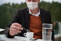 man in restaurant drinking coffee wearing face mask