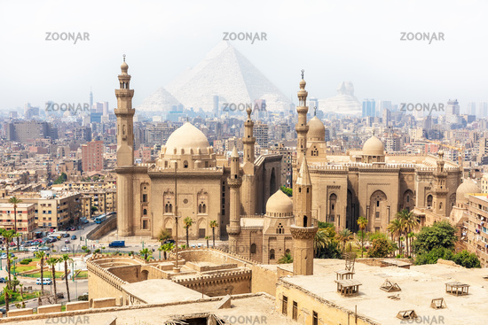 Mosque-Madrassa of Sultan Hassan and the Pyramids in the mist, Cairo, Egypt
