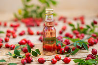 Rosehip oil in glass bottle with berries around from close up
