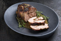 Barbecue marinated Greek lamb roast with herbs in gravy sauce as closeup on a modern design plate