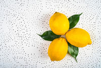 three lemons with green leaves are dotted on a white surface.