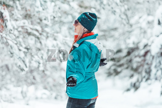 Woman standing out in falling snow in winter