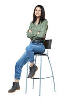 A young woman in jeans, boots and a khaki shirt is sitting on a high chair. Isolated on white.