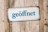 Old metal sign in front of a rustic wooden wall - Open - geoeffnet German