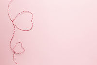 Valentine card. Heart shapes from red white string or rope. Pink background