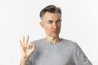 Close-up of satisfied middle-aged man in gray sweater, showing okay sign in approval, praising something good, standing over white background