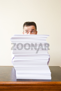 Businessman behind a stack of paper