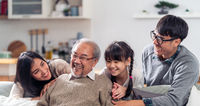 Happy multigenerational asian family portrait in living room panorama