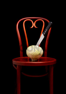 Knife stuck on a white cabbage put on a Thonet chair