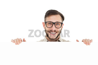 Geeky hipster showing poster smiling at camera