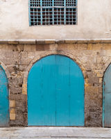 Closed turquoise weathered wooden arched door in stone bricks wall, in old abandoned district