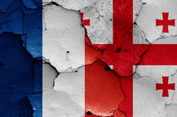 flags of France and Georgia painted on cracked wall