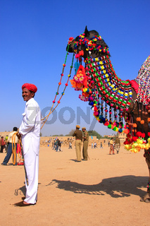 Indian man standing with his decorated camel at Desert Festival, Jaisalmer, India