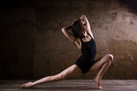 beautiful young girl dancer with long flowing hair in black clothes, a gymnastic swimsuit, in a dance pose on a wooden floor with a dark background. Dance theme Contemporary and Classics