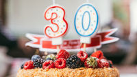 raspberries blackberry birthday cake with candles number 30 on defocused background. Selective focus macro shot with shallow DOF
