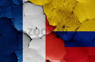 flags of France and Colombia painted on cracked wall