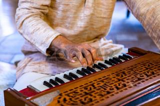 Male hands playing keys on harmonium