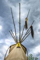 Oberes Ende eines  indianisches Tipis mit Stangen, Pferdeschweif und gelber Perlenverzierung vor wol