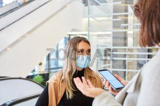 Passanten mit Coronavirus Warn-App auf dem Smartphone