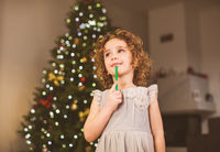 Little curly girl waititng for Christmas magic