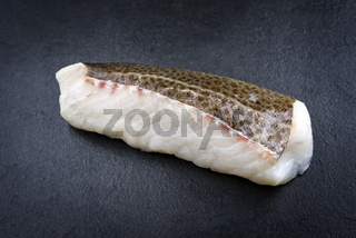 Raw Norwegian skrei cod fish filet with skin as closeup on black board with copy space