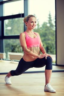 smiling woman stretching leg in gym