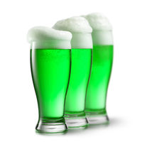 Green beer in glasses isolated on white background