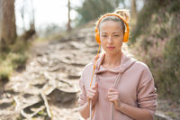 Portrait of beautiful sports woman with hoodie and headphones during outdoors training session.